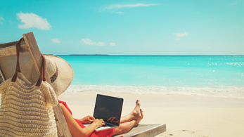 Woman on beach with laptop open - working remotely.